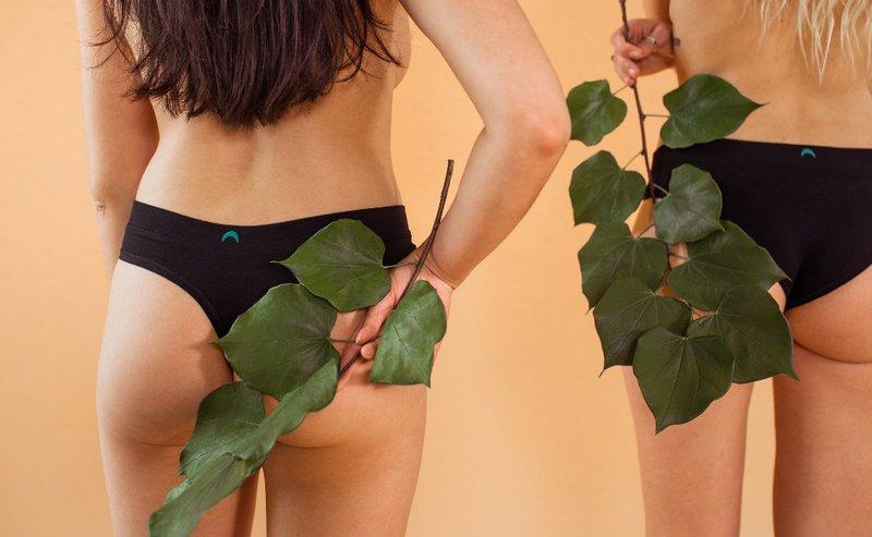 women in underwear holding leaves